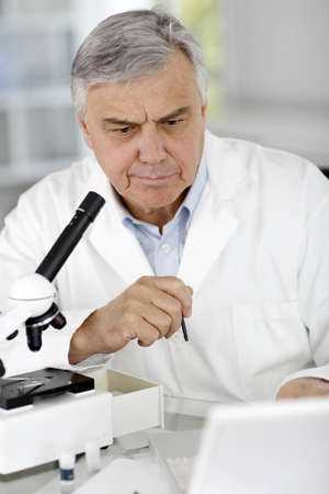Researcher in lab looking at laptop computer photo