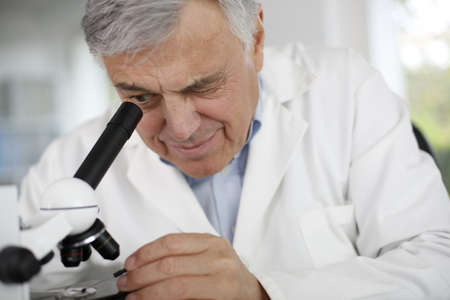 Scientist in lab looking through microscope lens photo
