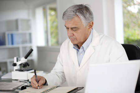 Doctor in biology writing report on agenda photo