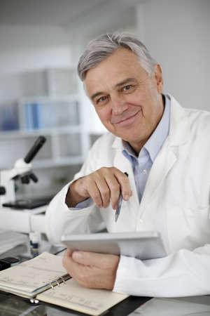 investigador cientifico: Retrato del cient�fico en laboratorio usando tableta digital Foto de archivo