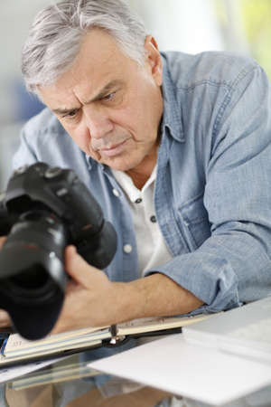 journalists: Photographer in office looking at camera screen Stock Photo