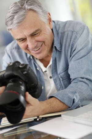 adventurer: Photographer in office looking at camera screen Stock Photo