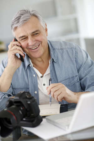 Photographer in office talking to client on the phone Stock Photo