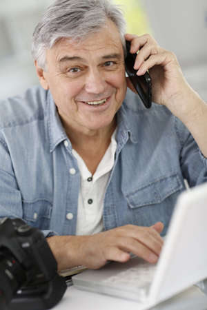 phonecall: Photographer in office talking to client on the phone