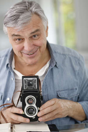 Senior photographer holding vintage camera photo
