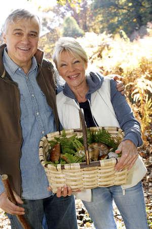 Senior couple in forest holding basket full of ceps mushrooms photo