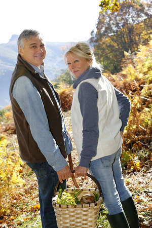 Senior couple in forest holding basket full of ceps photo