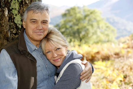 Portrait of smiling senior couple leaning against tree Stock Photo - 16321104