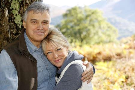 Portrait of smiling senior couple leaning against tree Stock Photo - 16321104
