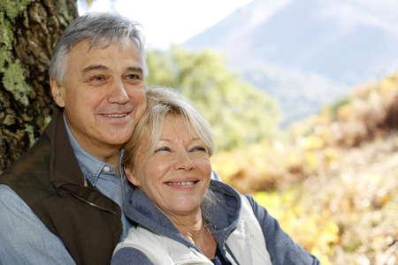 Portrait of smiling senior couple leaning against tree Stock Photo - 16320758