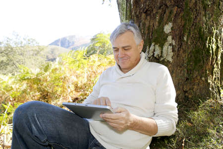 leant: Senior man leant againt tree websurfing on internet with tablet