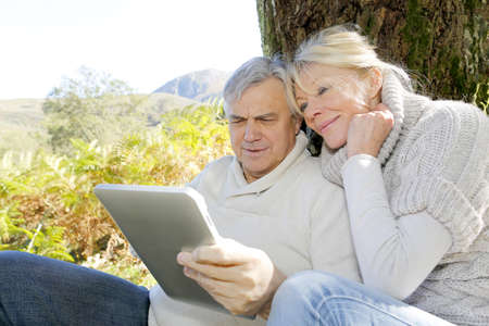 Senior couple using tablet in forest photo