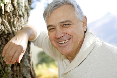 60 years old: Portrait of smiling senior man leaning against tree Stock Photo