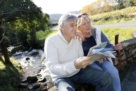 guy with walking stick: Senior couple sitting by river and looking at map Stock Photo