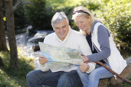 Senior couple sitting by river and looking at map photo