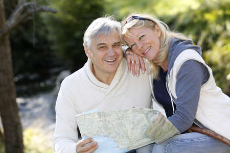 Closeup of happy senior couple sitting by river photo
