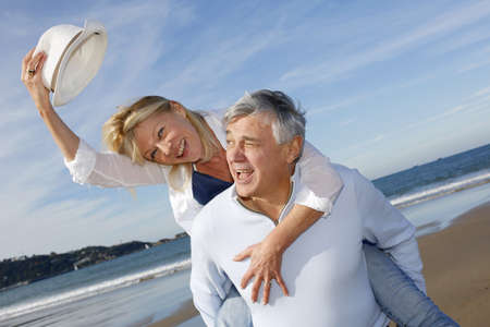 60 years old: Portrait of cheerful senior couple having fun at the beach