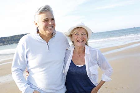 senioren wandelen: Senior paar wandelen op het strand in de herfst seizoen