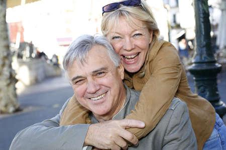 Portrait of senior man holding woman on his back photo