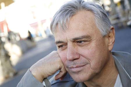 Portrait of smiling senior man standing outside photo
