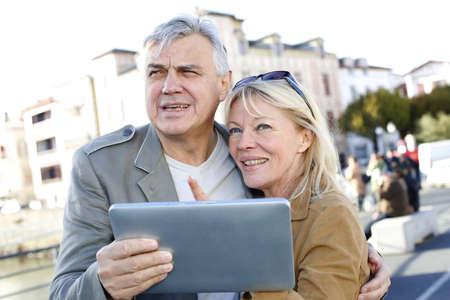 Senior couple using digital tablet in touristic area Stock Photo - 16320771