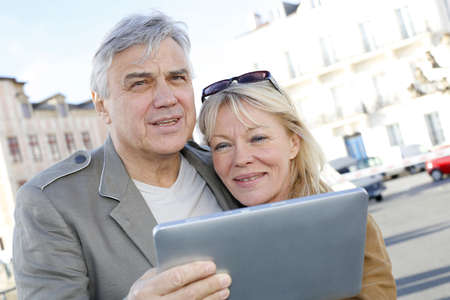 Senior couple using digital tablet in touristic area photo