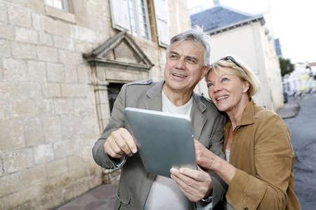 fiestas electronicas: Senior pareja que usa la tableta digital en el �rea tur�stica Foto de archivo