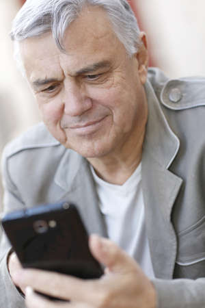 Portrait of senior man using smartphone in town  photo