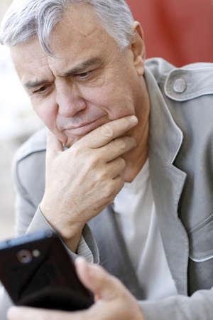 Portret van senior man met behulp van smartphone in de stad Stockfoto