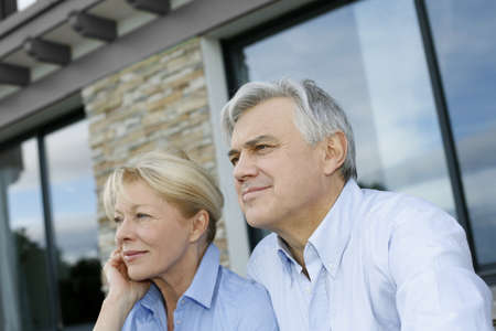retirement homes: Senior couple sitting in front of house and looking away Stock Photo