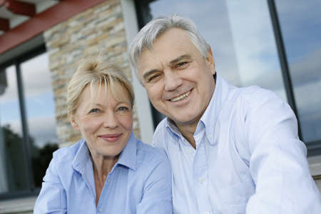 Cheerful senior couple looking at camera photo