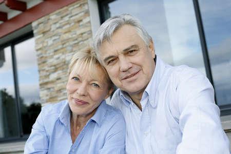 porch: Cheerful senior couple looking at camera