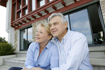 Senior couple sitting in front of house and looking away photo