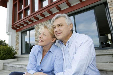 Senior Paar sitzt vor dem Haus und schaut weg