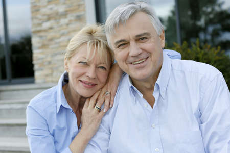 owners: Cheerful senior couple looking at camera