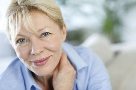 wise woman: Closeup of senior woman with blue shirt Stock Photo