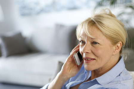 phonecall: Senior woman at home talking on mobile phone