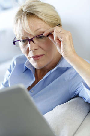 Senior woman with glasses using electronic tablet in sofa photo