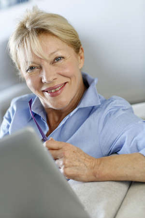 Senior woman using electronic tablet in sofa Stock Photo - 16398434