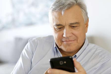 60 years old: Portrait of senior man using smartphone