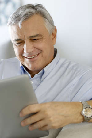 60 years: Senior man at home using electronic tablet Stock Photo