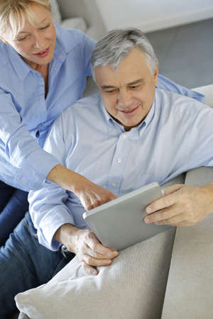 Modern senior couple websurfing on tablet photo