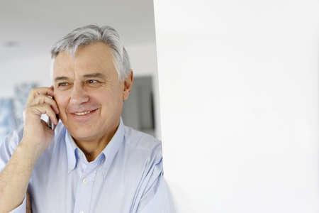 Aged man talking on mobile phone photo