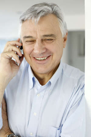 Aged man talking on mobile phone photo