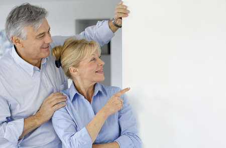 Senior couple pointing at message board photo