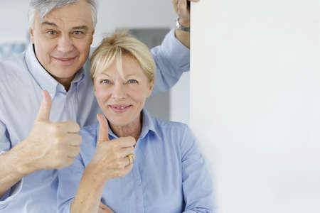 Senior couple showing thumbs up photo