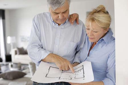 jubilados: Senior pareja en casa mirando anteproyecto
