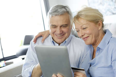 Senior couple doing shopping on internet photo