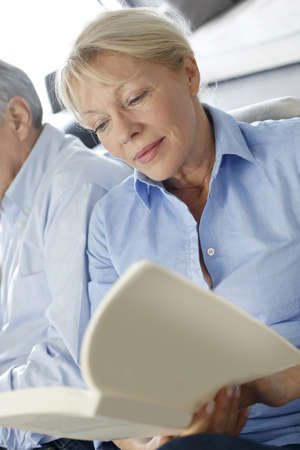 Senior woman reading book, husband sitting beside her photo