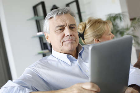 Senior man reading news on tablet sitting in couch photo